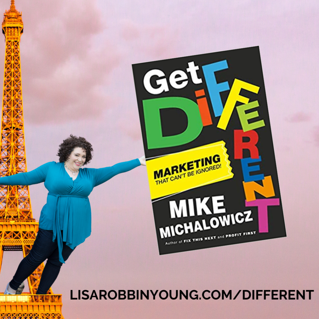"""A photoshopped image of a giant-sized Lisa, hanging from the Eiffel Tower, holding an even bigger copy of Mike's book, """"Get Different"""", with a caption featureing the URL to buy the book: Lisarobbinyoung.com/different"""